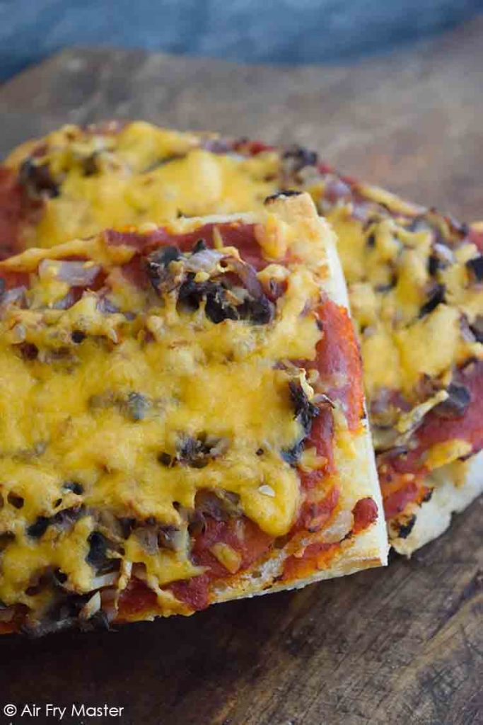 And up close view of these Air Fryer French Bread Pizzas on a cutting board.