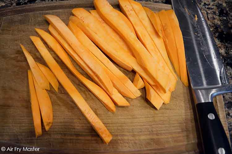 Cut the sweet potatoes into fries after peeling them.