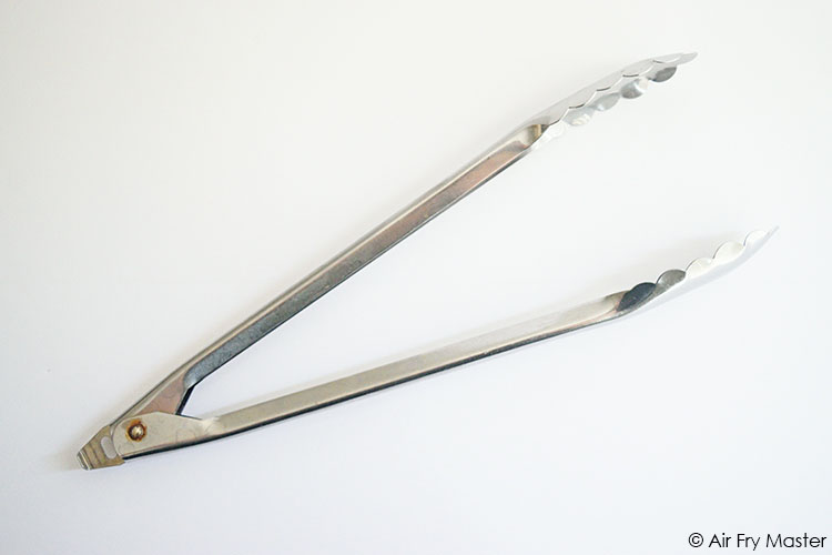 A single, aluminum tong on a white background.