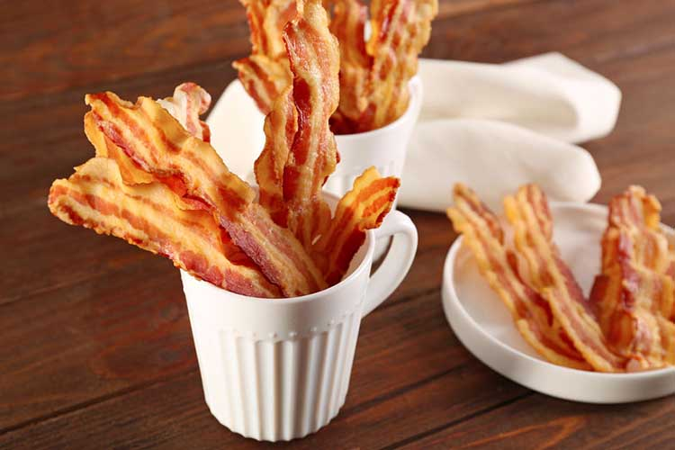 Cooked air fryer bacon in a cup and in a bowl.