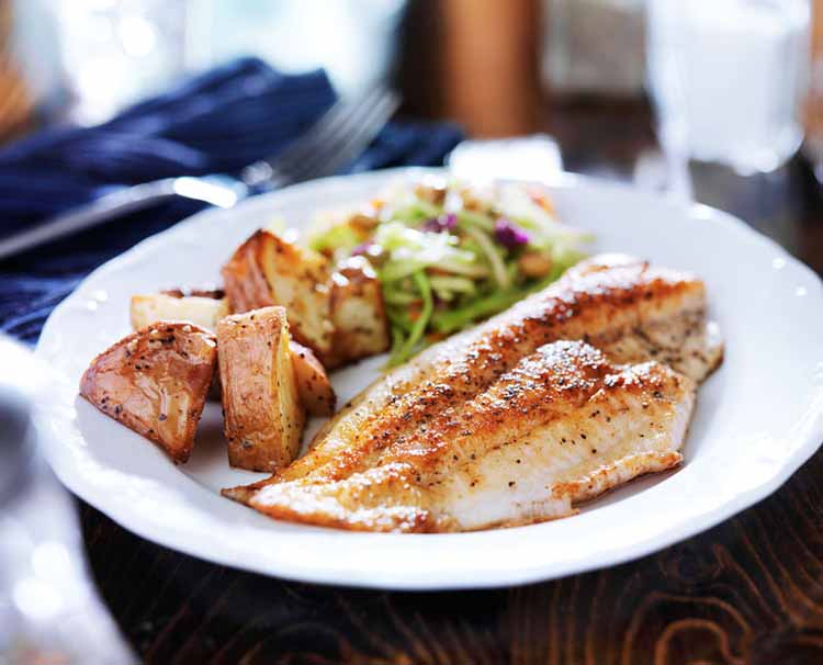 Fillet of fish with some roasted potato wedges and vegetables.