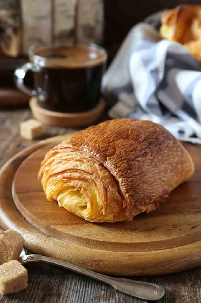 French breakfast: sweet puff pastry bun and cup of coffee