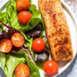 Air fryer salmon sits on a plate with a green salad.