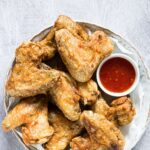 Cooked from frozen chicken wings on a round, white plate with red dipping sauce. One of many recipes in this guide to the best keto air fryer recipes.