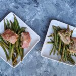 Air Fryer Pesto Chicken on two serving plates atop a bed of asparagus on each plate. One of many recipes in this guide to the best keto air fryer recipes.