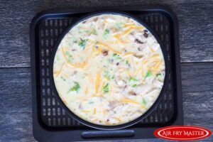 The filled quiche pan, set on the air fryer tray.