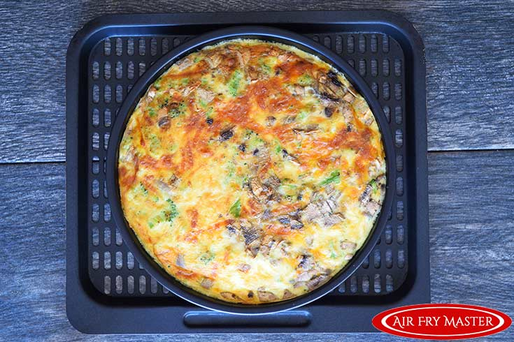 The air fried quiche, just out of the air fryer with a golden brown crust.