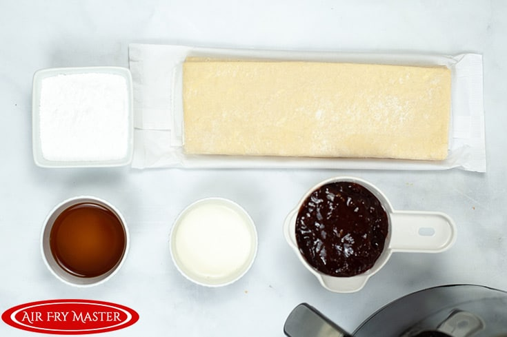 The ingredients in individual containers, ready to use. Pastry dough, jam, vanilla, heavy cream and powdered sugar.