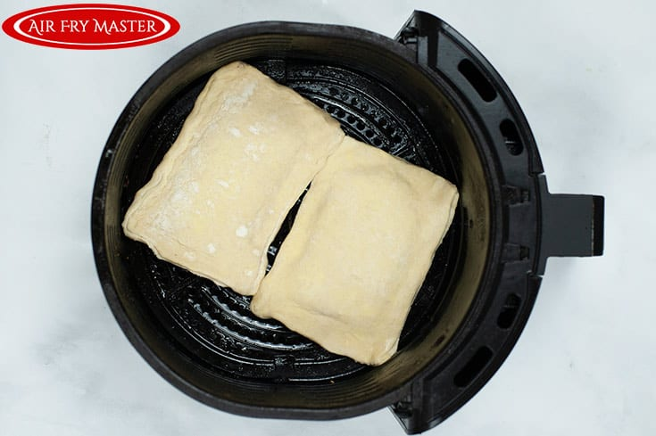Two raw pastries in the air fryer basket, ready to cook.