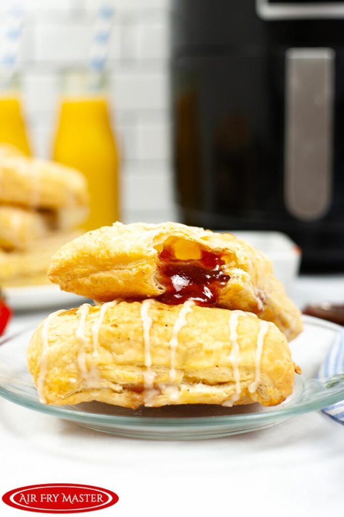 Two Air Fryer Toaster Strudels sit, one on top of the other, which some strawberry jam coming from the corner of the top pastry.