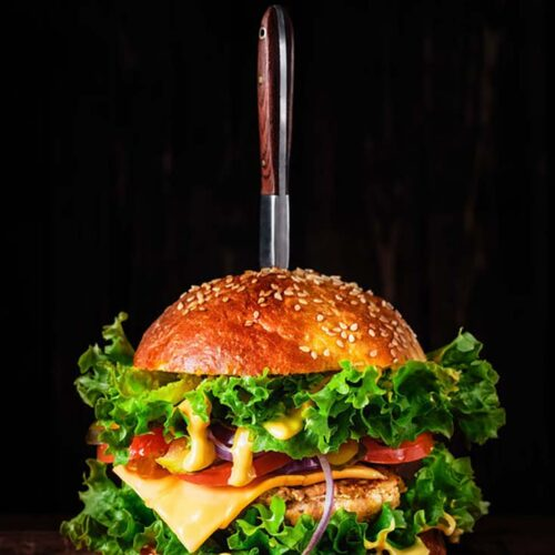 A single Air Fryer Turkey Burger with all the fixings. A knife sits upright in the middle of the burger. Cheese melts over the patties and lettuce in this Air Fryer Turkey Burgers Recipe.