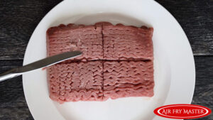 The ground turkey being cut into four equal portions.