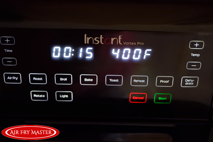 The control panel on the air fryer showing a time of 15 minutes and a temperature of 400 F.