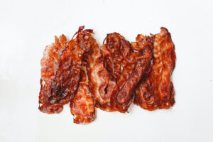 Cooked air fryer pork bacon on a white background.