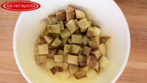 The seasoning sprinkled over the potatoes in the mixing bowl.