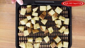 the potatoes spread out over an air fryer tray.