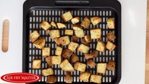 The finished Air Fryer Breakfast Potatoes cooling on the air fryer tray.