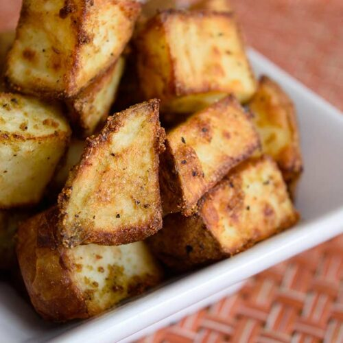 A side view of these Air Fryer Breakfast Potatoes in a white bowl.