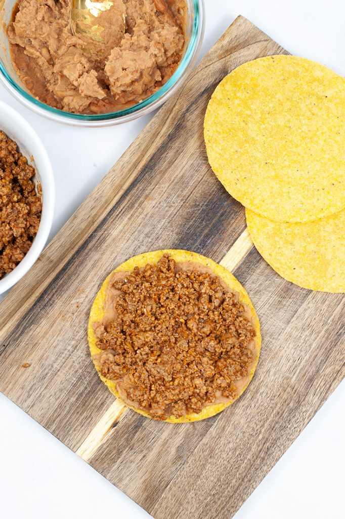 One tostada sits on a cutting board with beans and meat spread over it.