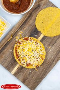 Cheese sprinkled over the top of a single tostada with beans and meat.