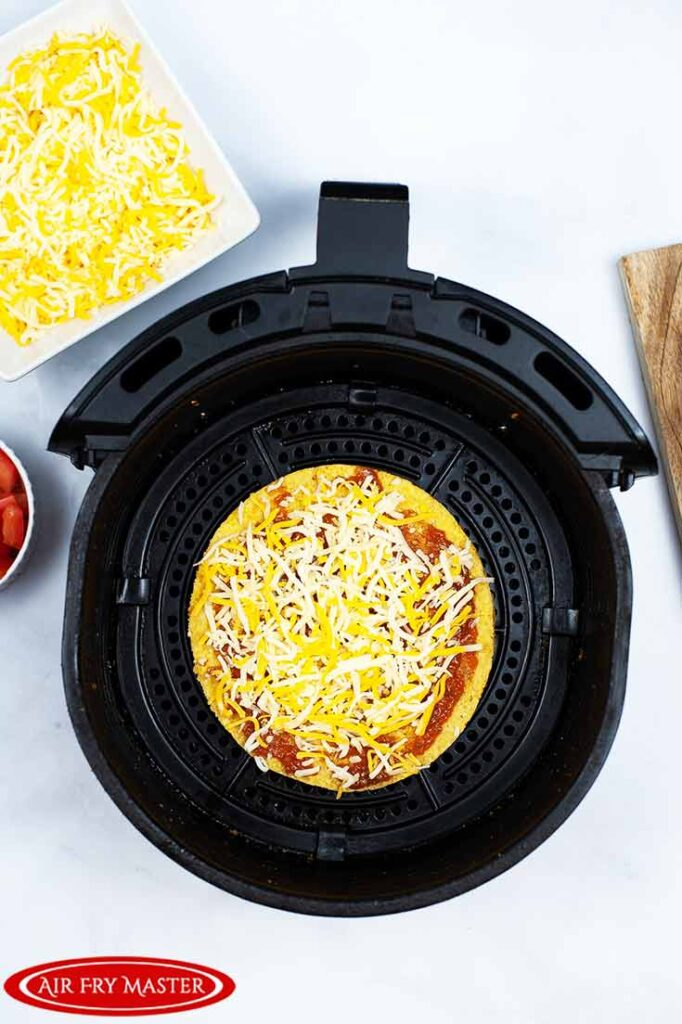 The uncooked Air Fryer Copycat Taco Bell Mexican Pizza sitting in an air fryer basket.