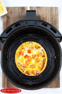 A cooked Air Fryer Copycat Taco Bell Mexican Pizza sitting in an air fryer basket, cooling.