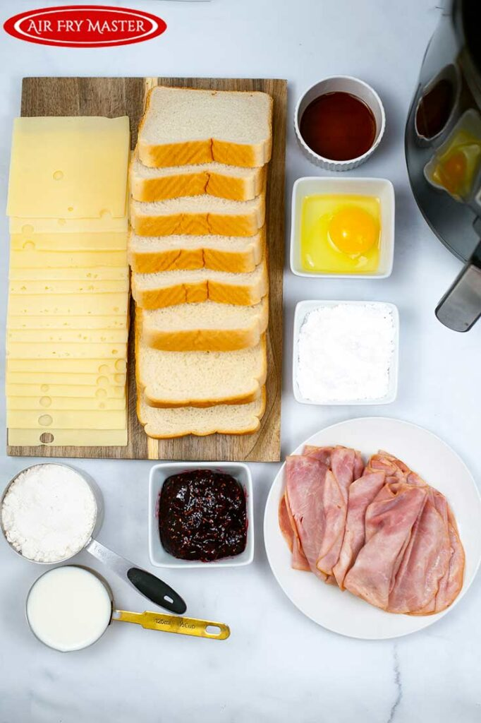All ingredients for this Air Fryer Monte Cristo Sandwich Recipe gathered around a cutting board and air fryer.