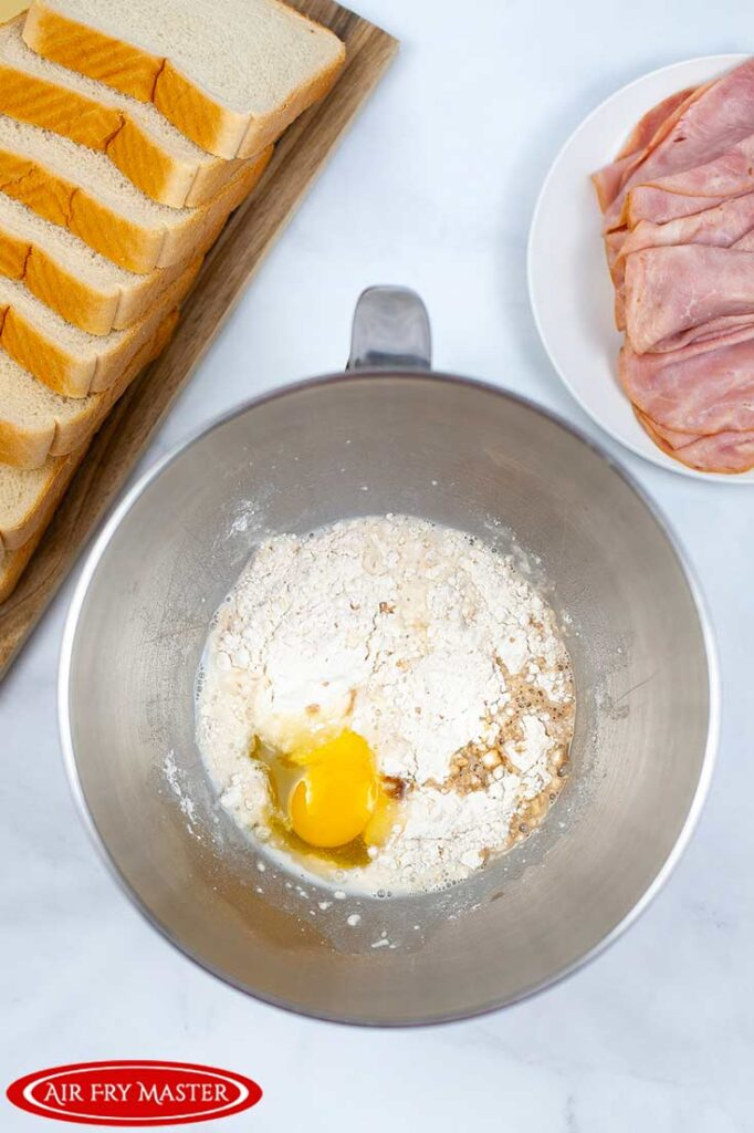 And overhead view of a metal mixing bowl with pancake mix and an egg in it.