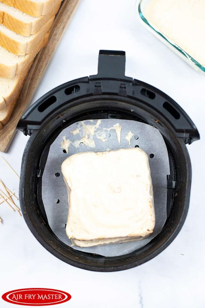 The Air Fryer Monte Cristo Sandwich covered in batter and sitting in a parchment lined air fryer basket.
