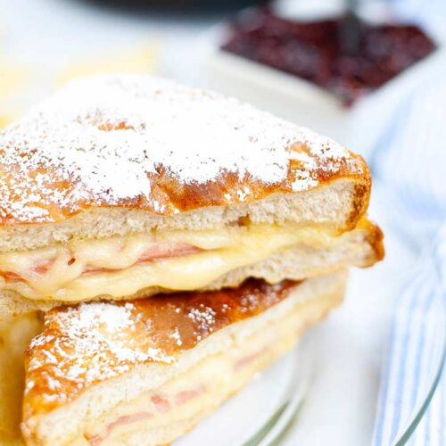 The finished Air Fryer Monte Cristo Sandwich, but in half an served on a glass plate.