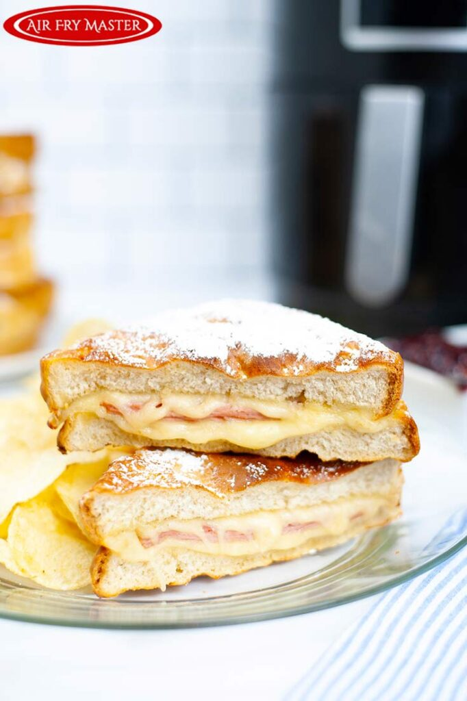 A front view of the cut Air Fryer Monte Cristo Sandwich on a plate with potato chips.