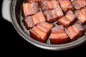 Cooked pork belly in a black crock.