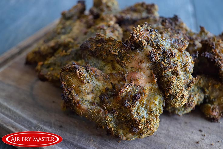 A side view of the finished Air Fryer Ranch Chicken Thighs sitting on a cutting board.