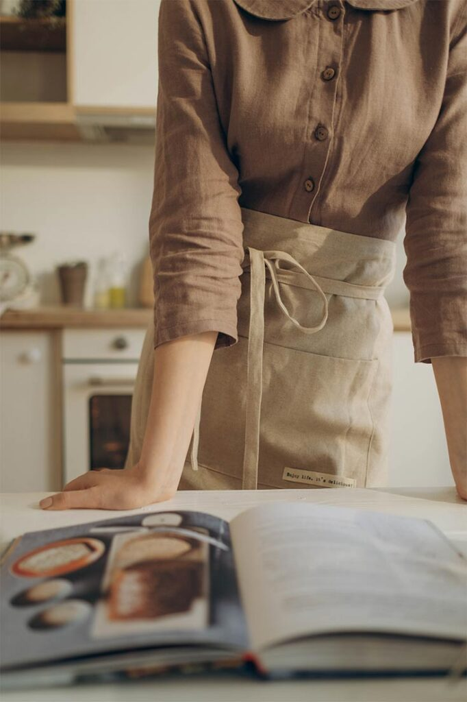 Woman stands at a counter which has a cookbook open, in this guide to the Best Air Fryer Cookbooks