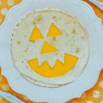 A single quesadilla on a white plate showing the final result of this Air Fryer Jack-O-Lantern Quesadillas Recipe