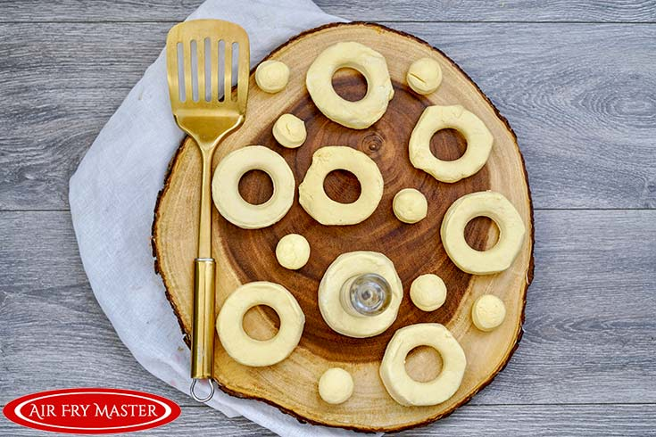 Cut donuts sit on a round wooden board.