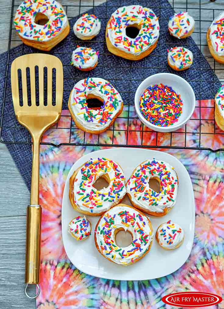 A white platter filled with Air Fryer Donuts Recipe With Sprinkles.