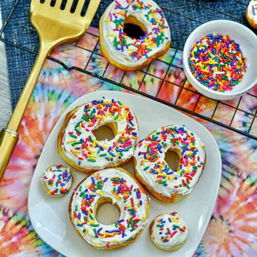 An overhead view looking down at a plate and cooling rack, both filled with this Air Fryer Donuts Recipe With Sprinkles.